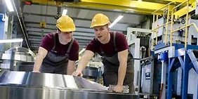 Zwei Männer, bekleidet mit bordeauxroten T-Shirts, dunklen Latzhosen und gelben Sicherheitshelmen, stehen in einer Fabrikhalle gebeugt über einem blankpolierten Metalltisch und besprechen etwas. Der rechts abgebildete Mann zeigt mit seiner rechten Hand auf etwas und schaut dabei in die Kamera. Der linke Mann schaut auf das, worauf der andere zeigt.
