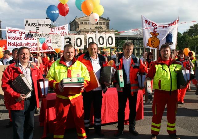 Mitarbeiter der Rettungsdienste mit Aktenordnern gehen in den Landtag