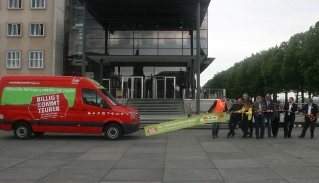 Verteter der Parteien und Gewerkschaften ziehen mit einem Seil an dem ein Transparent befestigt ist den DGB-Infobus