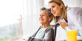Seniorin und Pflegerin blicken lächenlnd in die Ferne