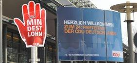 Plakat in Form einer stilisierten Hand mit Mindestlohnforderung neben dem Begrüßungsbilschirm zum CDU Bundesparteitag vorm der Messehalle Leipzig am 13.-15.11.2011