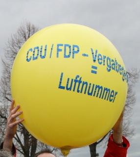 gelber Luftballon mit der Aufschrift CDU/FDP-Vergabegesetz = Luftnummer