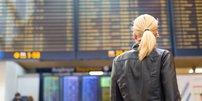 Frau mit Mund-Nasen-Schutz / Corona-Gesichtsmaske im Gesicht und Reisekoffer in der Hand (Symbolbild Urlaub in Corona-Zeiten)