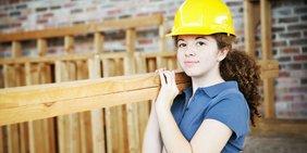 Junge Frau mit Schutzheln trägt Holzlatten